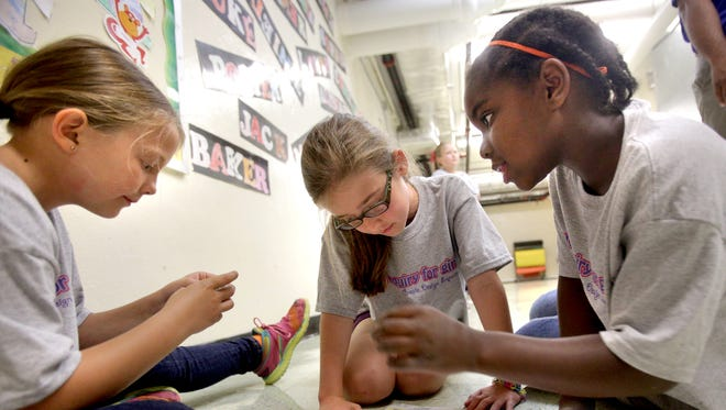 Eight-year-olds Keely Miga, Sydney Cuneo and Avery Stanley work on building a robot during a science club for girls at Campus School in Murfreesboro. 3. The club is funded by a Nissan/BEP minigrant.