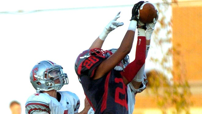 Elgin Comets receiver Bryston Williams goes up for a reception in front of a pair of Fredericktown defenders during high school varsity football action Friday night, Sept. 19, 2014, at Elgin High School.