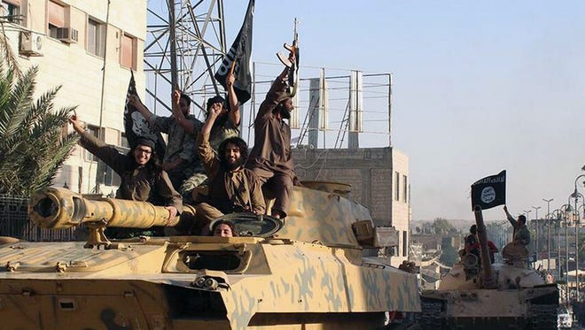 This image on June 30, 2014, shows fighters from the al-Qaida linked Islamic State group during a parade in Raqqa, Syria.