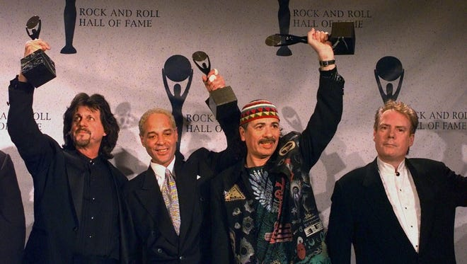 Carols Santana, second from right, holds up his trophy along with fellow Santana band members after the group was inducted into the Rock and Roll Hall of Fame on Jan. 12, 1998, in New York. From left, are: Gregg Rolie; Mike Carabello; Santana; and Michael Shrieve.