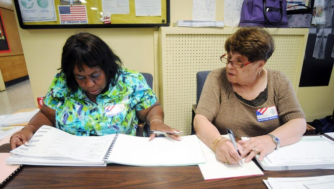 Elections inspectors Norma Vizcarrando, left, and Anita Cillo work on Tuesday during promary voting  at the Morse Young Child Magnet Elementary School in the City of Poughkeepsie. Sept. 9, 2014