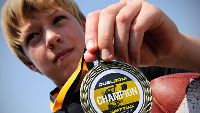 Kristoff Kowalkowski, 10, shows the medal he won at a national quarterback competition in his age group earlier this month at Paul Brown Stadium in Massillion, Ohio.  Kowalkowski was one of 150 young quarterbacks competing in the NFA's Fifth Annual Duel.