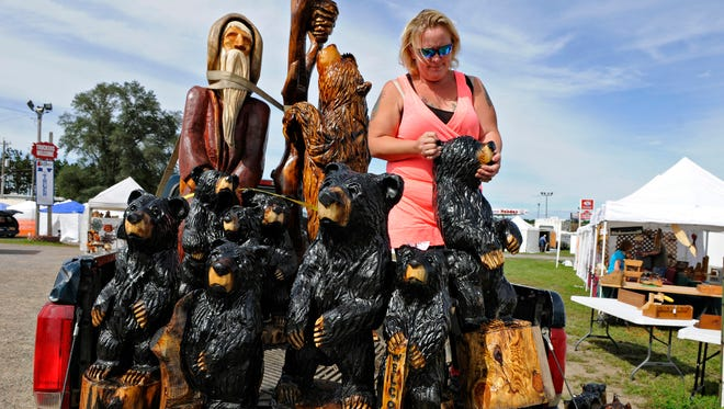 """Jennifer Davis, Motley, aka """"Just a Chick with a Saw,"""" unloaded her chain saw sculptures from her truck Friday in preparation for the Old Creamery Arts and Crafts Show in Rice. Davis also will be doing her chain saw carvings during the show for people to watch."""