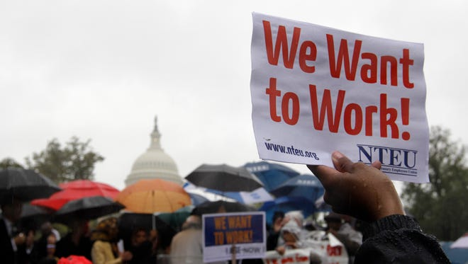 A protester holds up a placard during a rally to end the government shutdown on Capitol Hill in Washington.