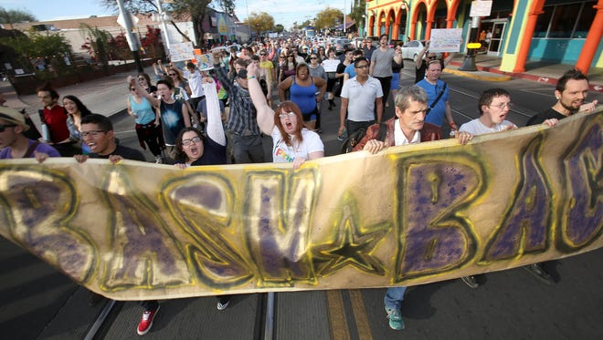 """Marchers protest against the religious freedom bill as they walk to the office of Arizona Gov. Jan Brewer on Feb. 21 in Tucson. Demonstrators want the governor to veto the bill. The protest sign reads """"Bash Back."""""""