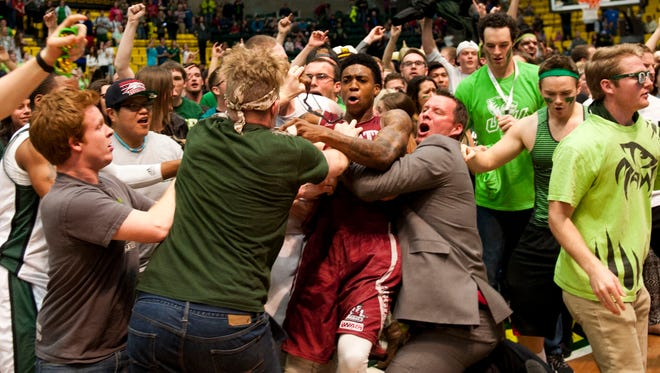 New Mexico State's Daniel Mullings, at center in red and white jersey, gets caught up in a brawl involving players and fans who came onto the court when New Mexico State guard K.C. Ross-Miller hurled the ball at Utah Valley's Holton Hunsaker.