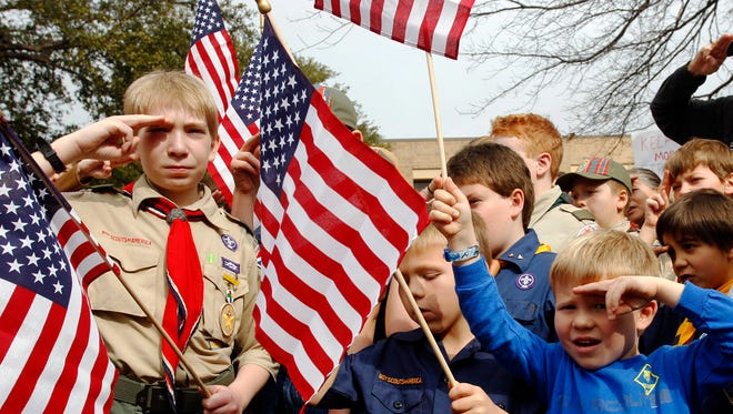 """From left, Joshua Kusterer, 12, Nach Mitschke, 6, and Wyatt Mitschke, 4, salute as they recite the pledge of allegiance during the """"Save Our Scouts"""" prayer vigil and rally against allowing gays in the organization in front of the Boy Scouts of America National Headquarters in Dallas, Texas."""