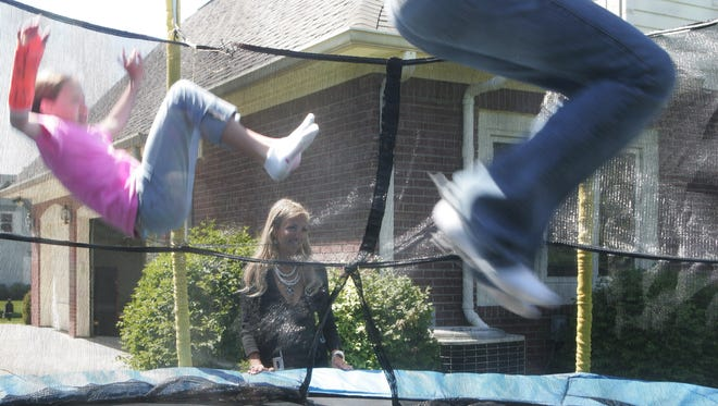 A mother watches her daughter and her friends on a trampoline at their home. Backyard trampolines were responsible for nearly 288,000 fractures from 2008 to 2011, an Indiana University School of Medicine researcher has found.
