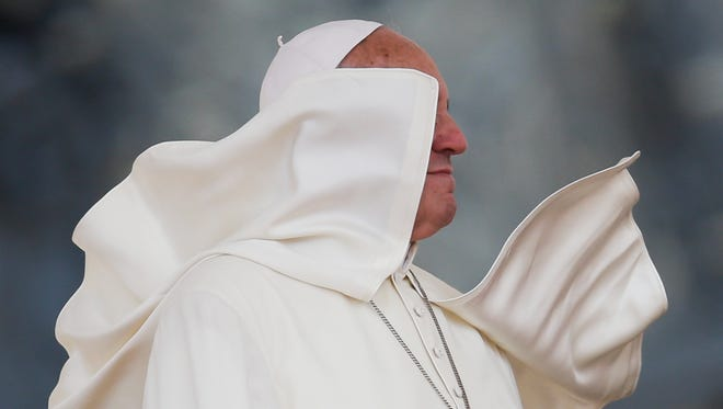 A gust of wind blows Pope Francis' mantle during an audience granted to catholic groups in St. Peter's Square at the Vatican.
