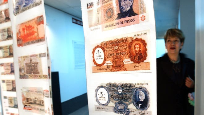 A woman looks at old currency during the opening of the Foreign Debt Museum in Buenos Aires.