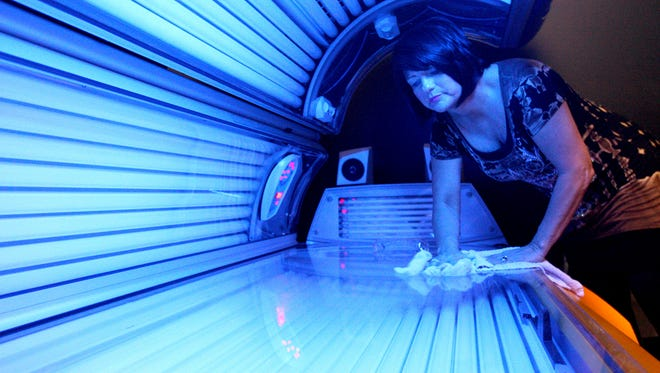 In this April 2, 2014 file photo, Teresa Lynch, owner of Dynamic Tanning in DeKalb, Ill., wipes down a tanning bed. T