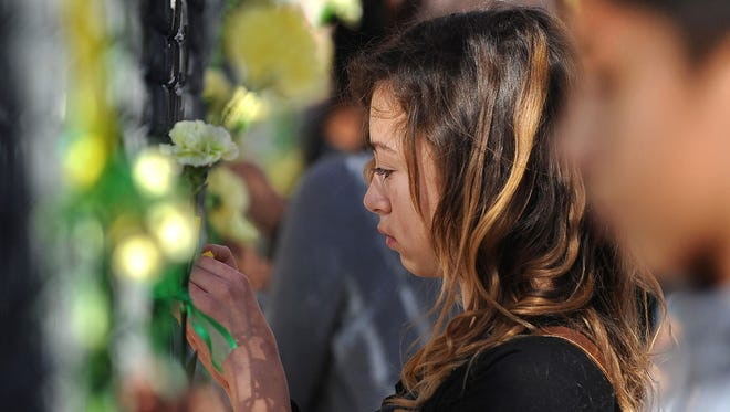 Students tie ribbons and yellow carnations along a fence on the side of Sparks Middle School where they attended a memorial for teacher Michael Landsberry in Sparks, Nev