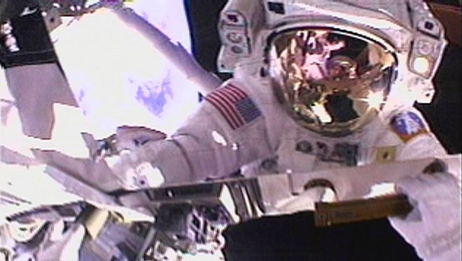 Astronaut Tom Jones sees his reflection and the Earth as he makes his way around the exterior of the International Space Station during a spacewalk in 2001.