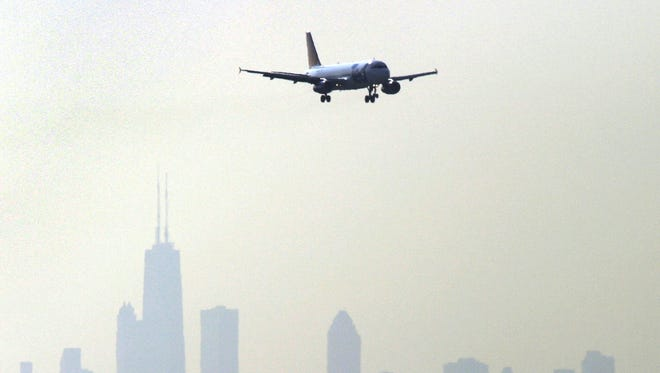 The Chicago skyline is silhouetted in the background as a plane comes in for a landing at Chicago O'Hare on July 15, 2004.