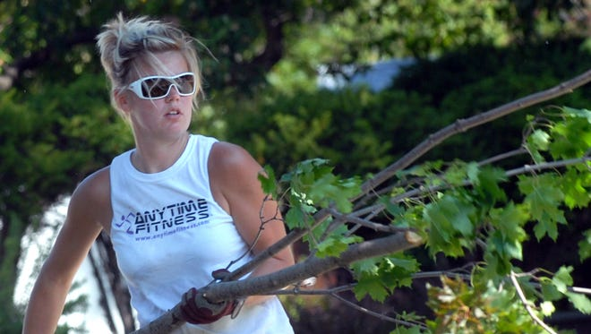 Vanessa Vandeberg, of Fond du Lac, throws brush into a trailer.