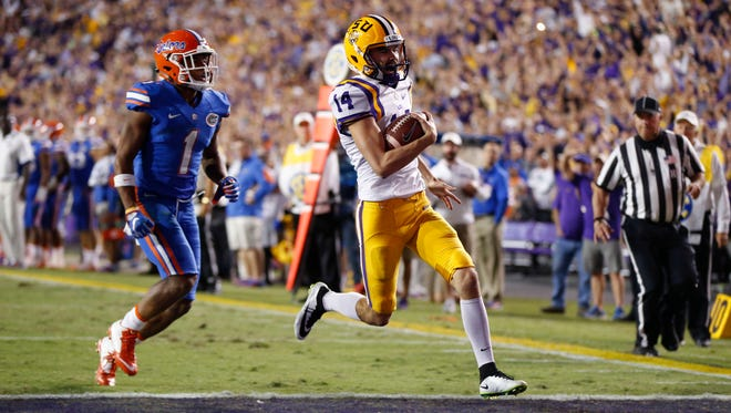 LSU place kicker Trent Domingue (14) carries for a touchdown in front of Florida defensive back Vernon Hargreaves III (1) on a fake field goal in the second half of an NCAA college football game in Baton Rouge, La., Saturday, Oct. 17, 2015. LSU won 35-28. (AP Photo/Gerald Herbert)