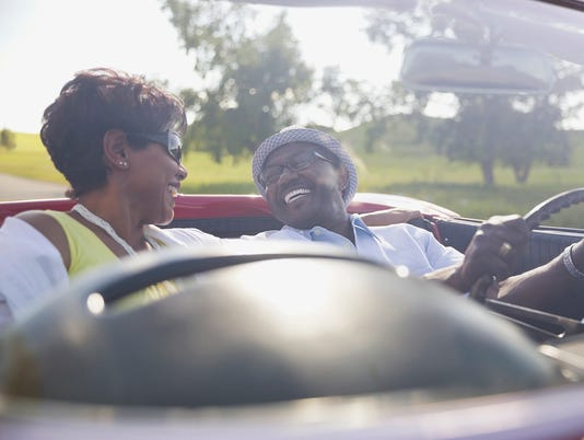 Happy couple enjoying road trip in convertible