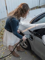 Elissa Potter plugs in Daisy to the 220v home charging station. A full charge takes about 4 hours at the station.