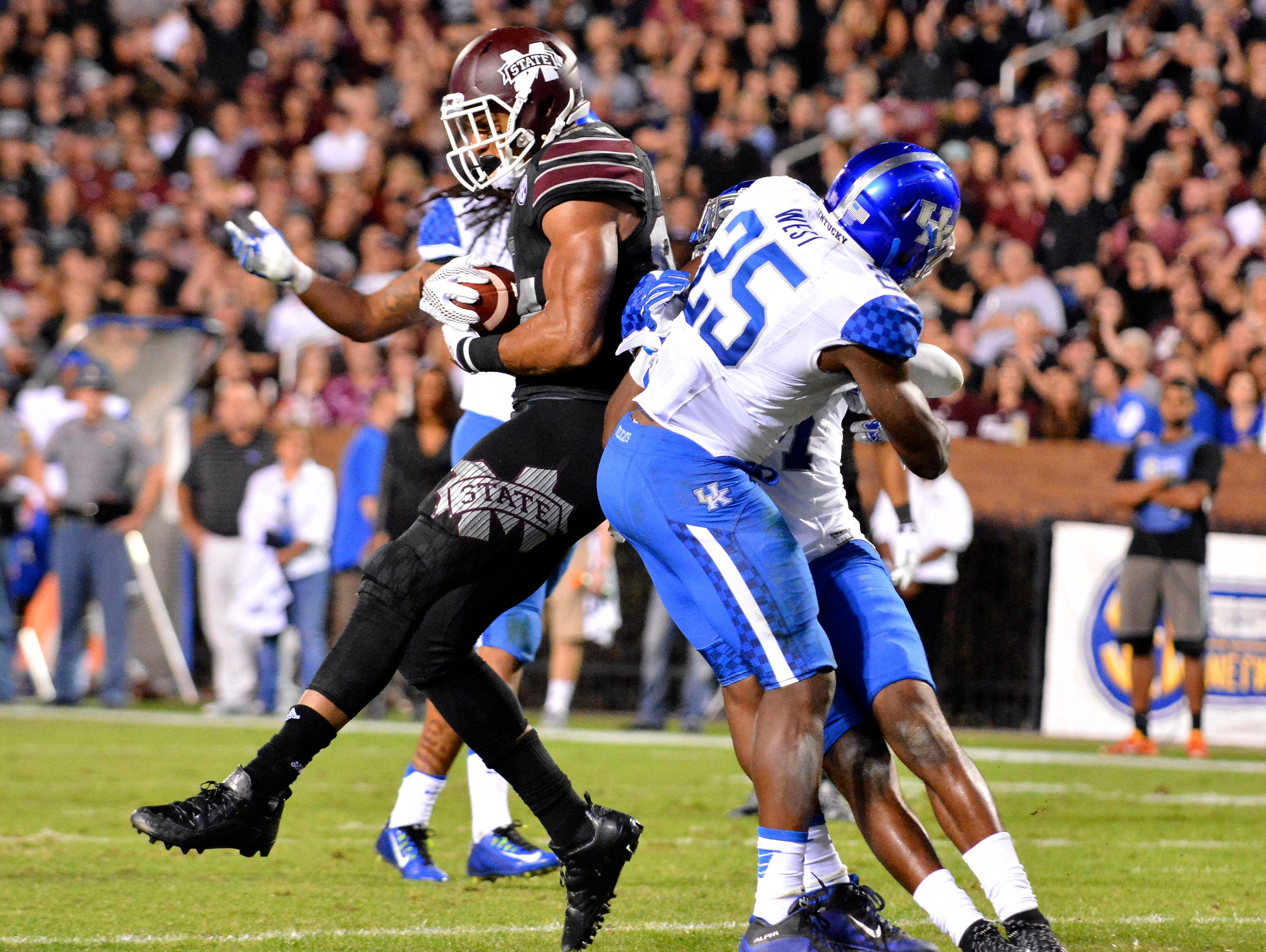 Oct 24, 2015; Starkville, MS, USA; Mississippi State Bulldogs tight end Darrion Hutcherson (84) comes down with a pass in the end zone as he is defended by Kentucky Wildcats safety Darius West (25) during the third quarter of the game against the Kentucky Wildcats at Davis Wade Stadium. Mississippi State won 42-16.