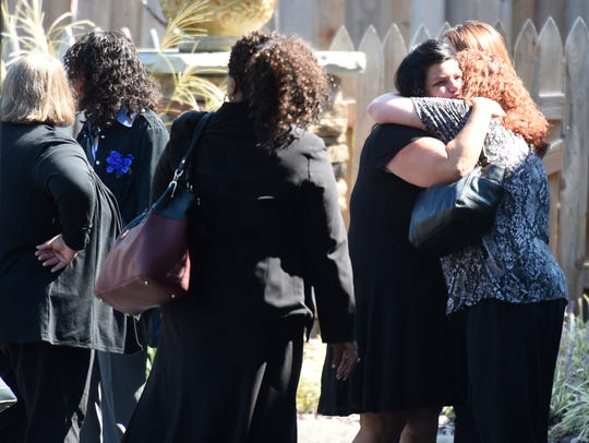 Friends and family enter the funeral for Melanie Crow