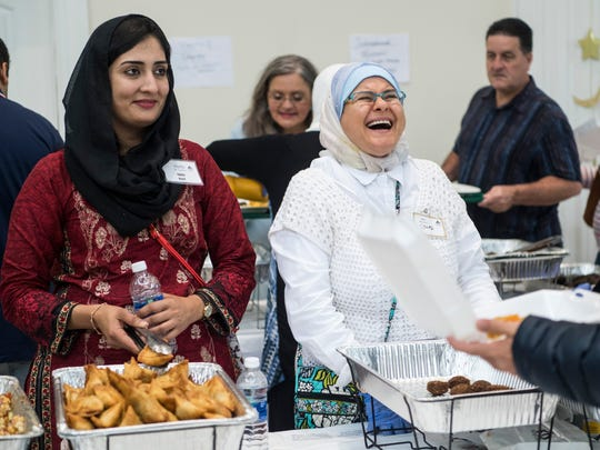 Rabia Nasir (left) and Souad Sibai (right) greet and laugh with customers as they serve up food during the 16th annual International Food Festival at the Islamic Society of Evansville in Newburgh, Ind., Sunday, Oct. 8, 2017.
