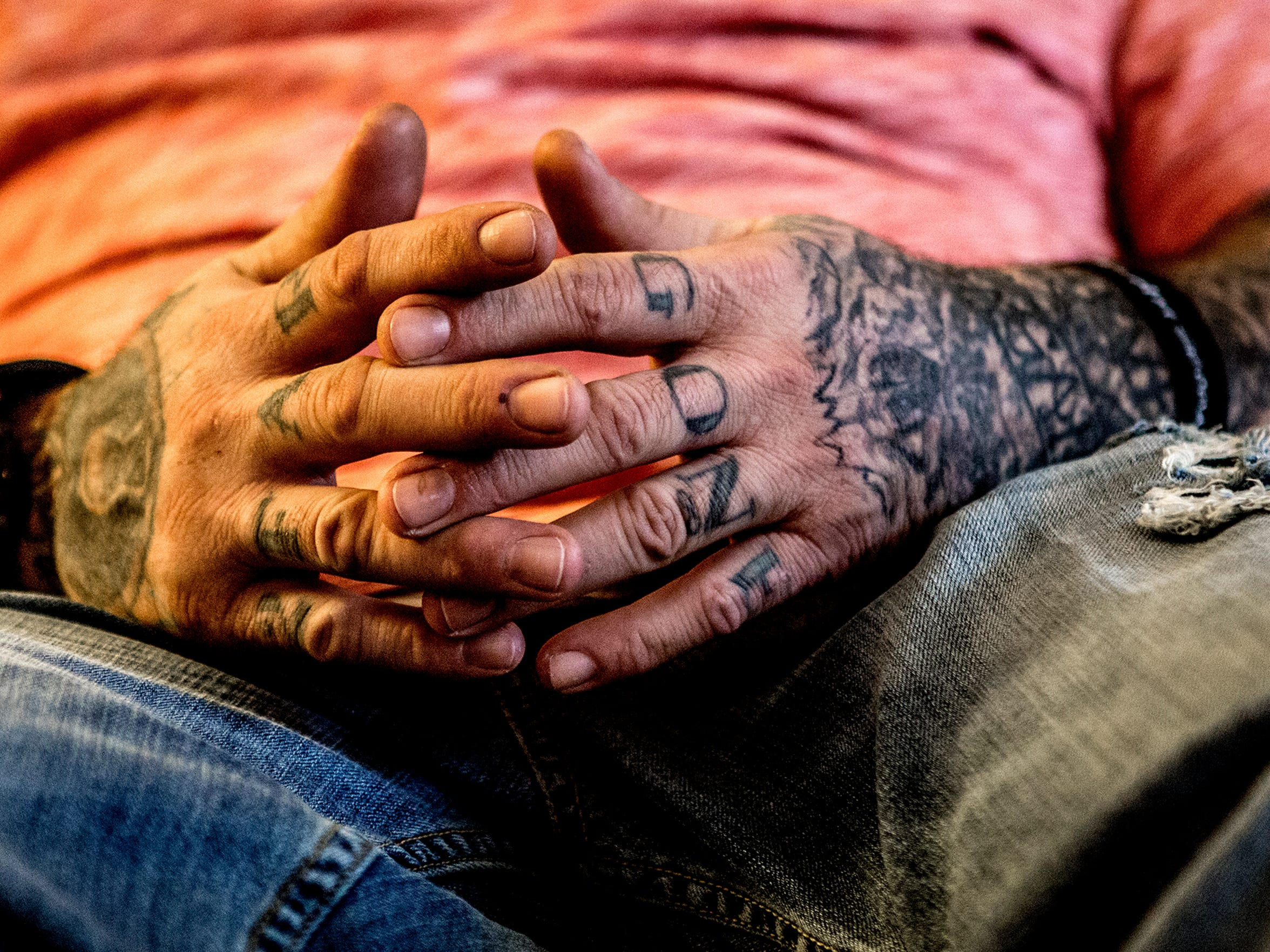 William Rector folds his tattooed hands while speaking about his addiction and recovery. Rector credits the Newark Addiction Recovery Initiative with saving his life.