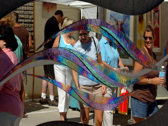 Artstreet visitors are reflected in a piece of three-dimensional, laminated glass artwork.