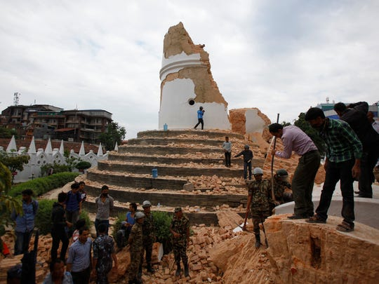 Volunteers work to remove debris at the historic Dharahara