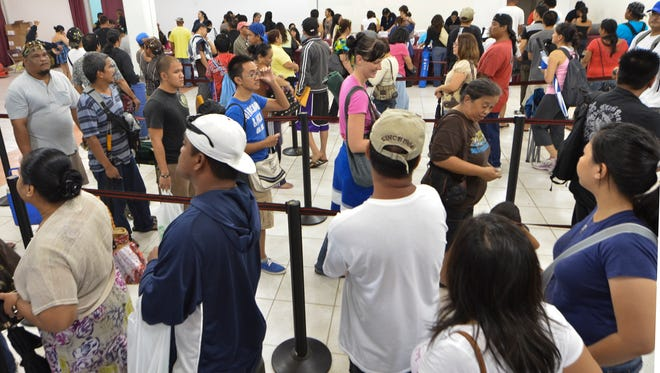 In this Dec. 3, 2011, file photo, residents line up to pick up their past-due tax refund checks at the Micronesia Mall.