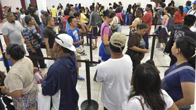 In this Dec. 3, 2011 file photo, residents line up to pick up their past-due tax refund checks at the Micronesia Mall in Dededo.