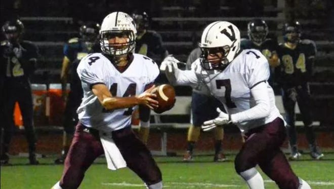 Senior quarterback Zack Zaccone (14) hands the ball off to junior running back CJ Lavery (7) in a September 2016 game.
