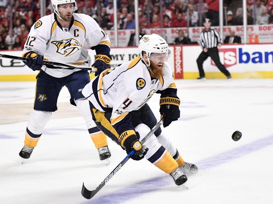 Nashville Predators defenseman Ryan Ellis (4) goes after a puck as Nashville Predators center Mike Fisher (12) skates behind him in the second period of game two in the first-round NHL playoff series at the United Center, Saturday, April 15, 2017, in Chicago, Ill.