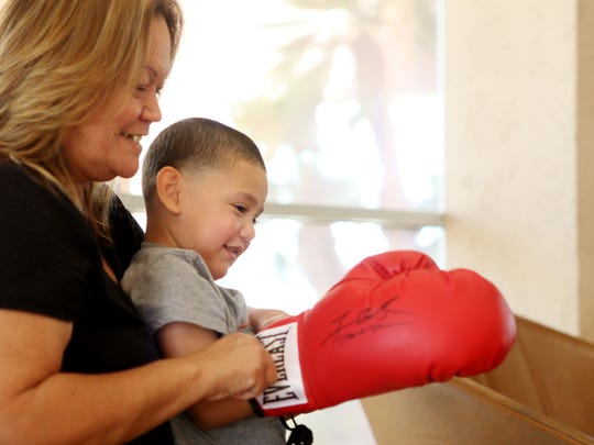 Indio resident Rozena Ramirez helps grandson Julian Rios, 3, put on a boxing glove autographed by boxer Tim Bradley  at The Desert Sun offices Tuesday.