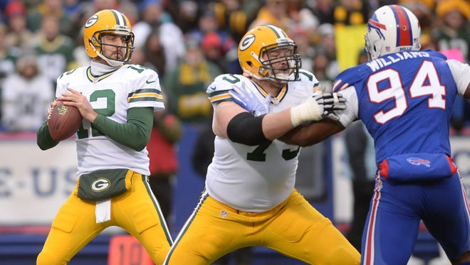 Green Bay Packers quarterback Aaron Rodgers (12) tries to find a receiver behind the block of Bryan Bulaga (75) on Mario Williams (94) against the Buffalo Bills at Ralph Wilson Stadium in Orchard Park, N.Y., December 14, 2014.