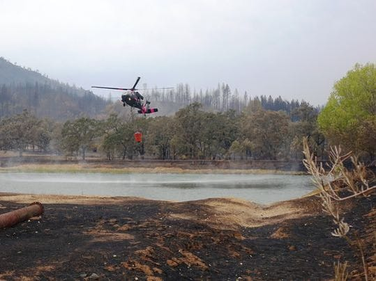 A CalGuard helicopter hovers over a burned vineyard in Middletown, Calif. on Sept. 15, 2015, as it prepares to fill its drop bucket to dump on the raging Valley Fire. Firefighters are increasingly calling upon military technology to help them battle wildfires. Helicopters like this one can fly at night because the pilots may wear night-vision goggles.
