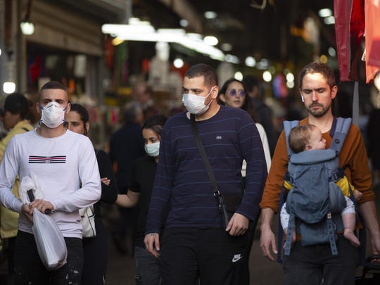 People wear face masks as they shop at a food market in Tel Aviv, Israel, Monday, March 16, 2020.