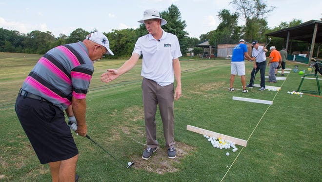 Daniel Bowden works with Rocky Kelly on her golf swing as Bowden's brother Jonathan works with John Dockery during a lesson at Shanks driving range in Piedmont on Thursday, July 14, 2016.