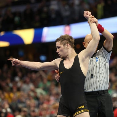 Iowa's Spencer Lee celebrates after winning the 125