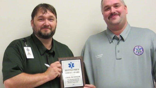 Capt. Craig Weninger, AEMT, left, and Director Stephen Graybill, right, accept awards during National EMS Week.