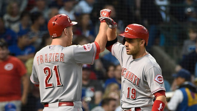 Cincinnati Reds first baseman Joey Votto (19) is greeted by third baseman Todd Frazier (21) after hitting a home run against the Chicago Cubs during the fourth inning at Wrigley Field.