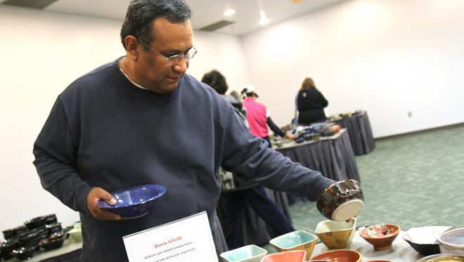 Dean Howard shops for bowls during San Juan College's Hospice Charity Bowl Sale in  December 2012.