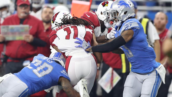 Quandre Diggs, left, and Darius Slay tackle Cardinals receiver Larry Fitzgerald in the first quarter of the Lions' 35-23 win Sunday, Sept. 10, 2017 at Ford Field.