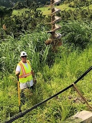 Highland Township resident and DTE lineman Dave Stoyk is pictured working on a steep incline in Puerto Rico.
