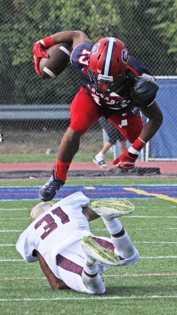 Stepinac wide receiver Devante Reid flies over Iona Prep's Lionel Lucas, Jr. after a reception during a varsity football game at Stepinac High School Sept. 19, 2015. Stepinac crushed Iona Prep 48-6.