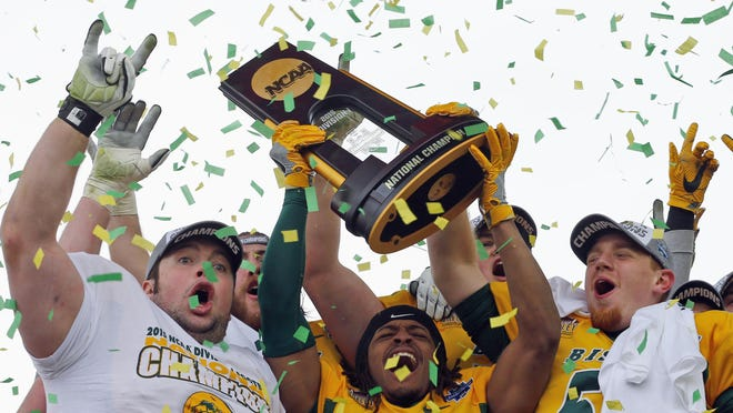 North Dakota State players celebrate on Jan. 9 with the trophy after they defeated Jacksonville State 37-10 in the FCS championship game in Frisco, Texas. The Bison have won five straight FCS titles.