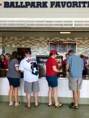 Fans order at a concession stand inside Hammond Stadium