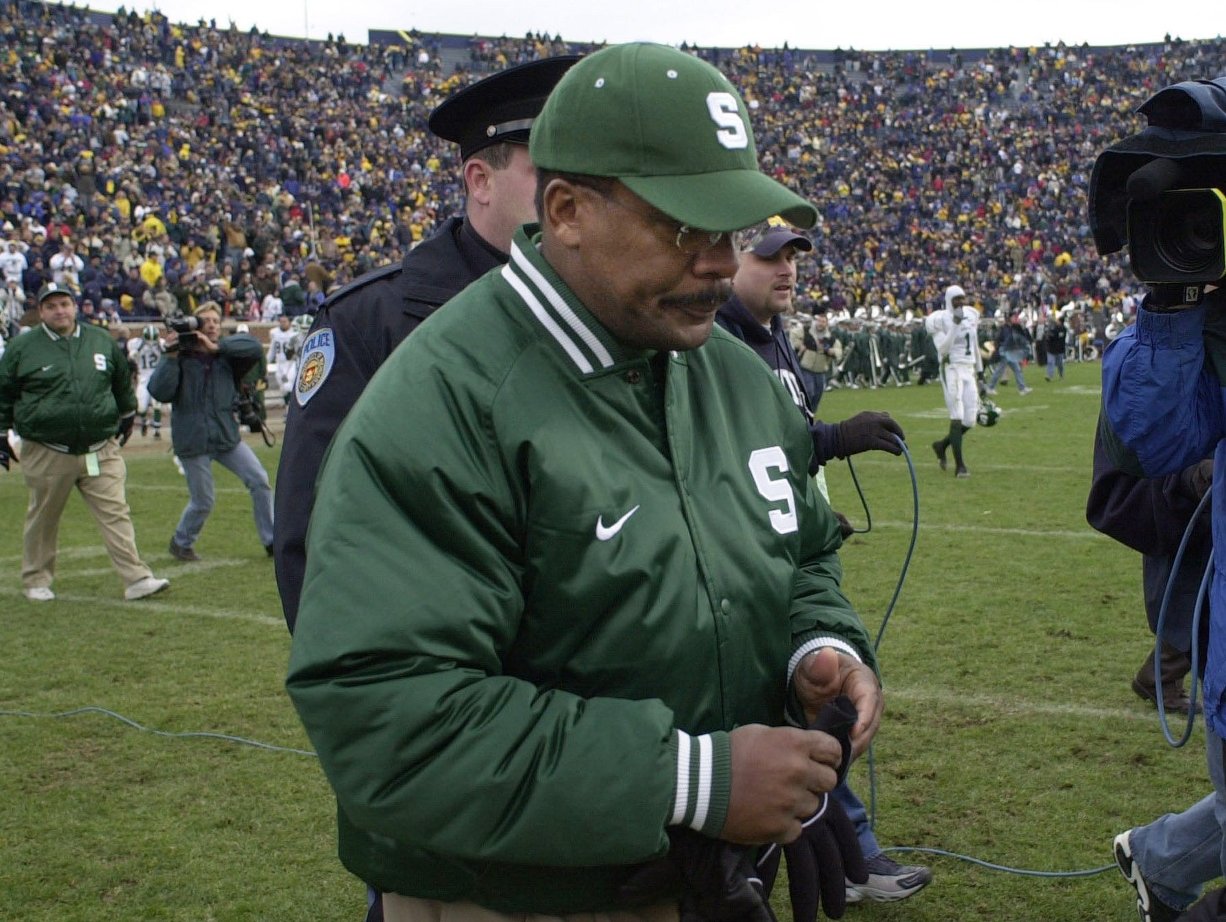 Michigan State coach Bobby Williams walks to midfield to meet Michigan head coach Lloyd Carr after Michigan State's 49-3 loss on Nov. 2, 2002 in Ann Arbor. Williams was fired on Nov. 4, 2002, two days after the Spartans dropped to 3-6 with their worst loss in 55 years.