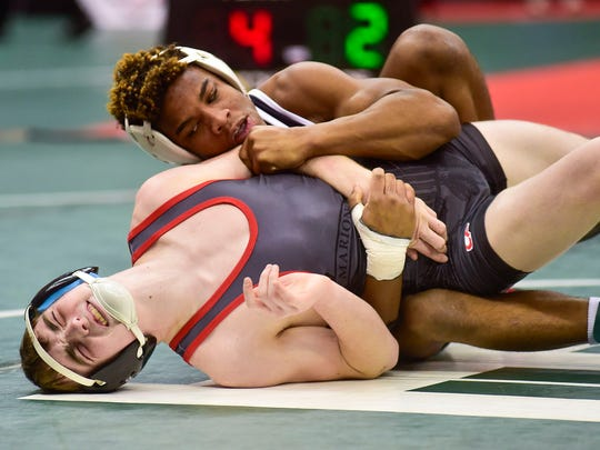 Marion Harding's Mason Sparks cringes with pain as he is held by Mason's Jaimen Hood during the 126-pound Division I match at the state wrestling tournament last season. Mason had previously injured his ribs in his match on Thursday.