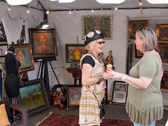 Artist Vickie Milam (left) talks with a festivalgoer