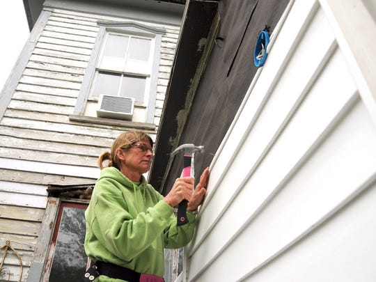 Kim Degler of Orwigsburg, Pa., a volunteer with United Methodist Committee on Relief, nails siding to a home in Crisfield that was damaged during Hurricane Sandy.